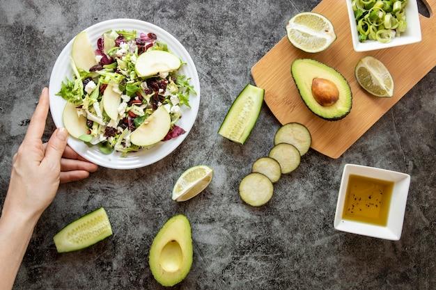 Deliciosa ensalada con aguacate sobre tabla de madera