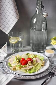 Deliciosa ensalada césar fresca con pollo sobre un fondo gris