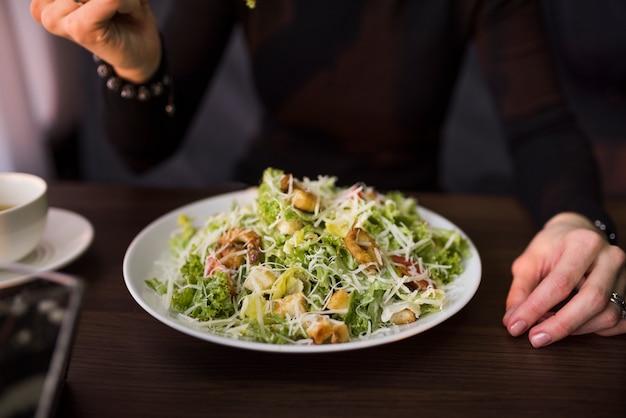 Deliciosa ensalada con crutones; camarones y queso parmesano rallado en la mesa frente a una persona