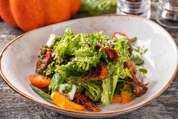 Deliciosa ensalada de otoño con calabaza, espárragos, lechuga, tomates secos y queso. ensalada saludable de otoño