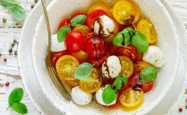 Deliciosa ensalada de verano de tomates cherry amarillos y rojos, mozzarella con albahaca y especias.
