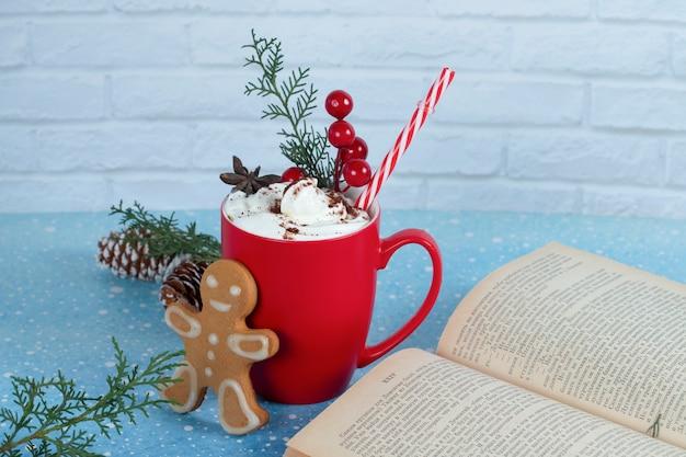 Deliciosa galleta de jengibre, libro y taza de café roja sobre superficie azul. .