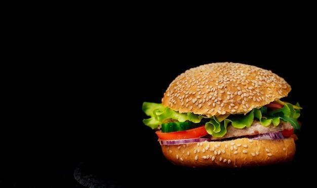 Deliciosa hamburguesa con carne y verduras frescas aisladas en negro