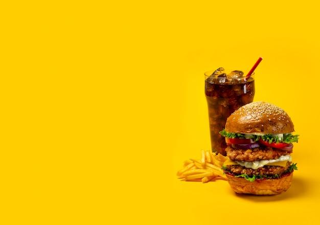 Deliciosa hamburguesa con cola y papas fritas sobre un fondo amarillo