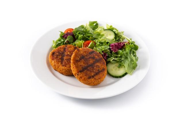 Deliciosa hamburguesa de garbanzos saludable y ensalada aislado sobre fondo blanco.