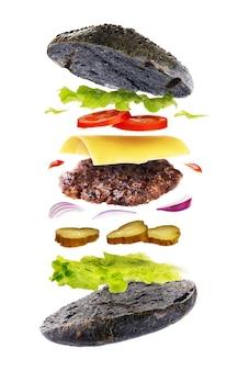 Deliciosa hamburguesa con pan de color negro aislado sobre un fondo blanco.