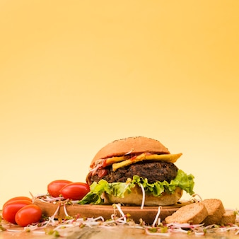 Deliciosa hamburguesa con tomates cherry; brotes y rebanadas de pan en la tabla de cortar contra el fondo amarillo