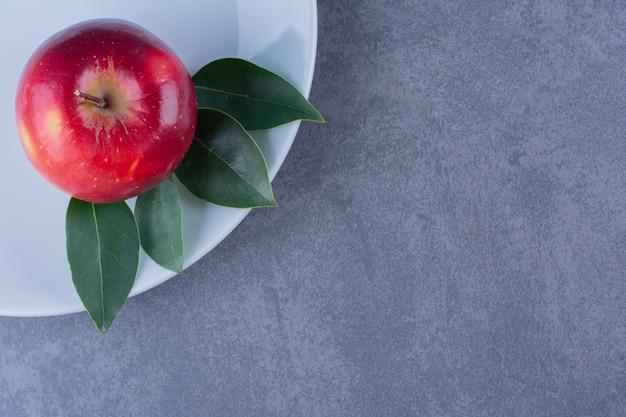 Deliciosa manzana con hojas en placa sobre mesa de mármol.