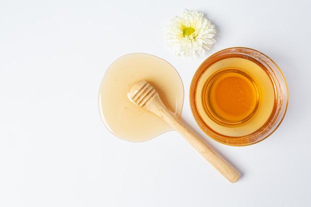 Deliciosa miel con cucharón de miel de madera sobre superficie blanca