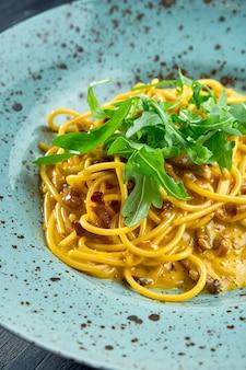 Deliciosa pasta carbonara italiana con tocino y yema cruda, parmesano y rúcula. pasta casera servida en una placa azul sobre una superficie oscura