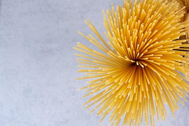 Deliciosa pasta cruda sobre superficie blanca