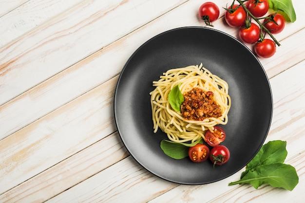 Deliciosa pasta italiana clásica boloñesa con tomates en un plato sobre un fondo blanco de madera.