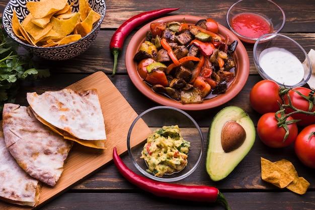 Deliciosa pita junto a la comida entre nachos con salsas y verduras.