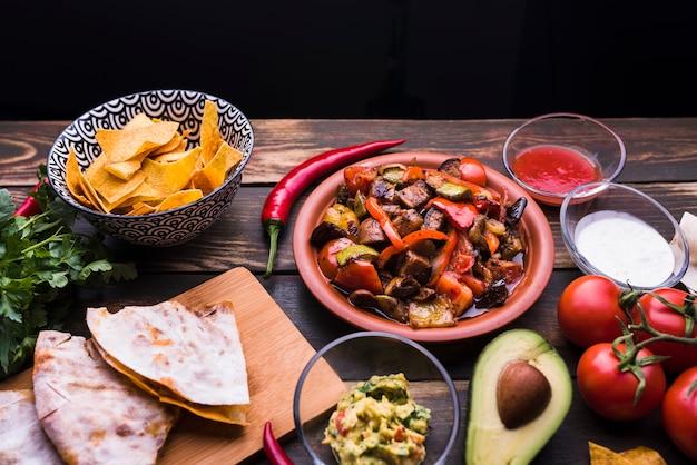Deliciosa pita junto a la comida entre verduras y nachos.