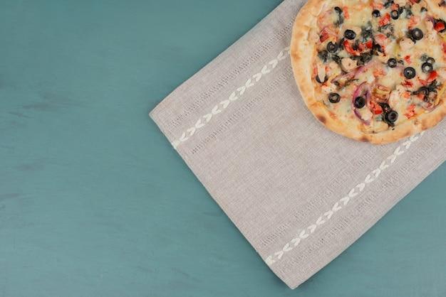 Deliciosa pizza caliente con aceitunas y tomates en superficie azul.