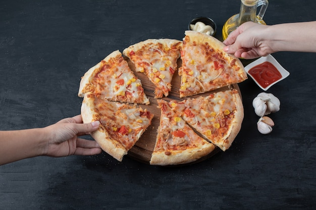 Deliciosa pizza casera fresca. mano femenina que toma la rebanada de pizza. gran angular.