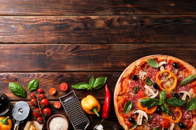 Deliciosa pizza e ingredientes sobre fondo de madera, espacio de copia