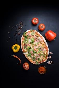 Deliciosa pizza con ingredientes y especias sobre papel tapiz.