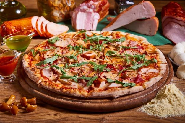 Deliciosa pizza italiana servida en mesa de madera. pizza en rodajas sabrosa composición de pizza