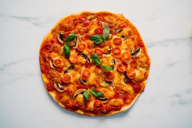 Deliciosa pizza margherita sobre superficie de piedra blanca. pizza margarita casera con tomate, albahaca y queso mozzarella. copie el espacio, vista desde arriba.
