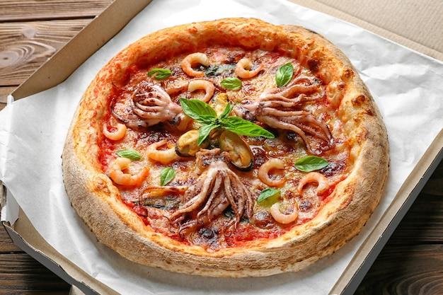 Deliciosa pizza de mariscos en caja de dibujos animados, cerrar