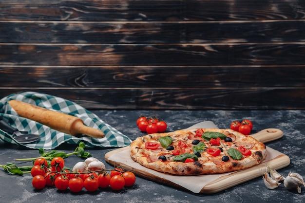 Deliciosa pizza napolitana a bordo con tomates cherry, espacio libre para texto