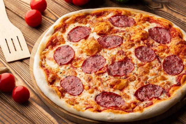 Deliciosa pizza de pepperoni casera caliente en la mesa de madera. pizza de pepperoni - pizza casera fresca con salsa de pepperoni, queso y tomate sobre fondo de piedra negra rústica con espacio de copia.