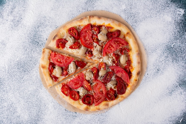 Deliciosa pizza de pollo con tomates en mármol.