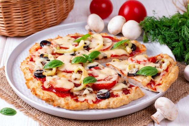Deliciosa pizza en rodajas con pollo, tomates y mozzarella sobre la mesa. horizontal