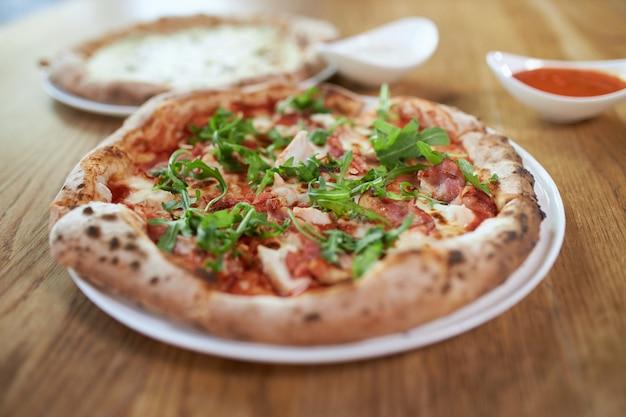 Deliciosa pizza con rúcula de jamón y salsa cercana