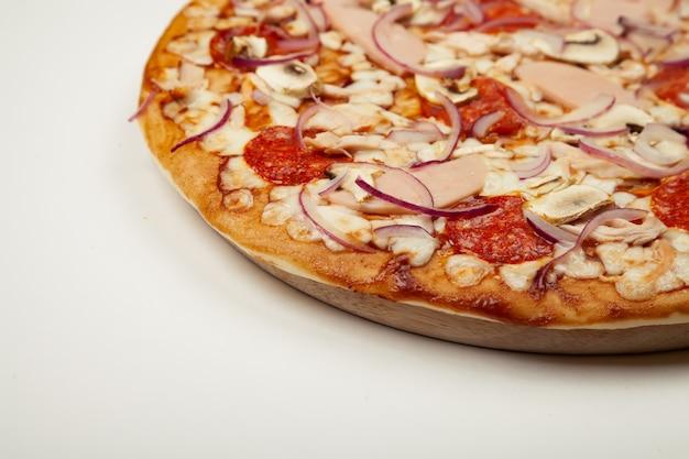 Deliciosa pizza con salsa bbq, queso mozzarella, jamón, pepperoni, pollo ahumado, champiñones, cebolla morada. de cerca.