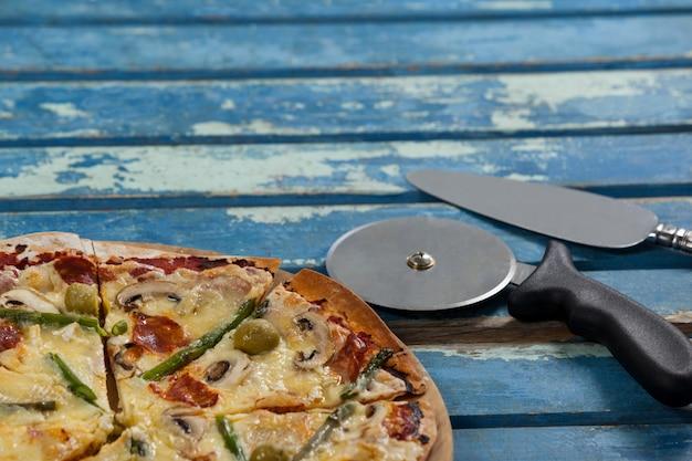 Deliciosa pizza servida en bandeja de pizza con cortador y cuchillo en tablón de madera