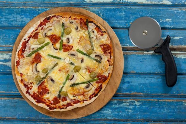 Deliciosa pizza servida en bandeja de pizza con cortador en tablón de madera