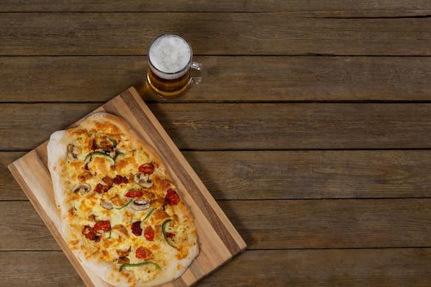 Deliciosa pizza servida en bandeja de pizza con un vaso de cerveza en tablón de madera