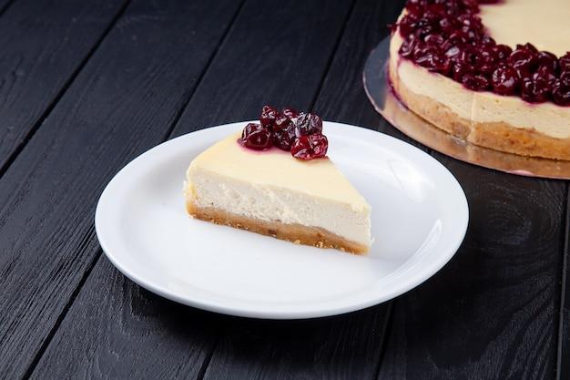 Deliciosa rebanada de pastel de queso con cereza en plato blanco. pastel sobre fondo oscuro. postre comida para receta o menú. copia espacio cheesecake de vainilla y cereza