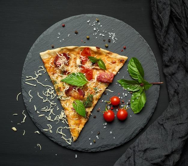Deliciosa rebanada de pizza triangular con salchichas ahumadas, champiñones, tomates, queso y hojas de albahaca