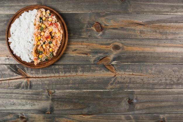 Deliciosa receta de arroz cocido en plato de madera sobre la mesa.