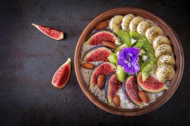Deliciosa y saludable avena con higos, kiwi, plátano, almendras y semillas de chía. mesa negra desayuno saludable. comida de fitness. nutrición apropiada. endecha plana. .