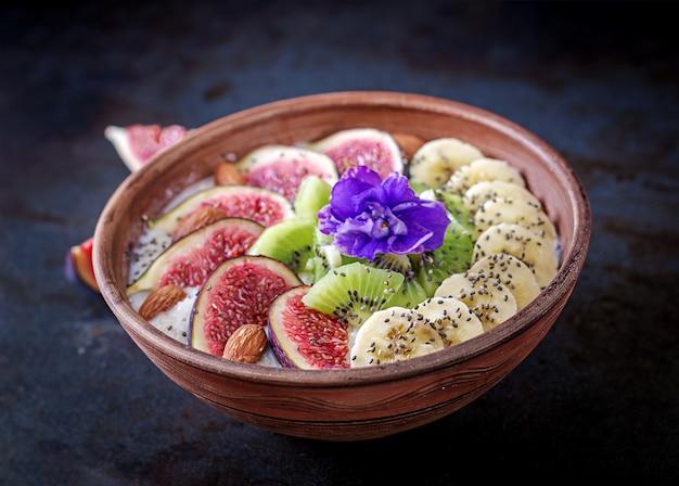 Deliciosa y saludable avena con higos, kiwi, plátano, almendras y semillas de chía. mesa negra desayuno saludable. comida de fitness.