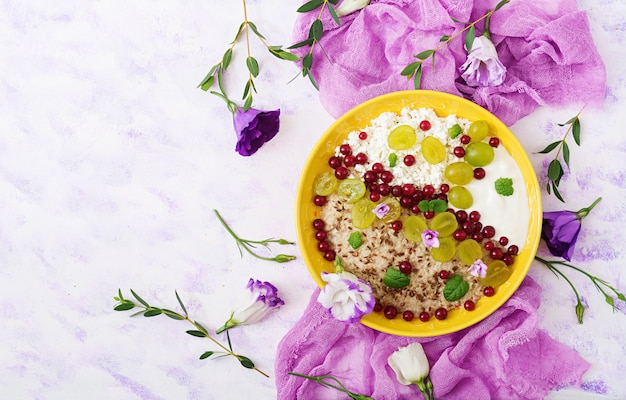 Deliciosa y saludable avena con uvas, yogurt y requesón. desayuno saludable. comida de fitness. nutrición apropiada. endecha plana. vista superior.