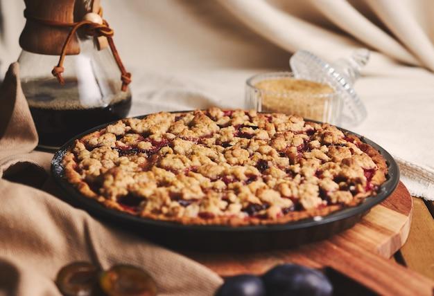 Deliciosa tarta de ciruela con café chemex e ingredientes con tela sobre una mesa de madera con tela