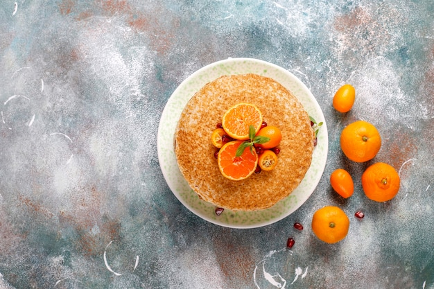 Deliciosa tarta crepe casera decorada con semillas de granada y mandarinas.