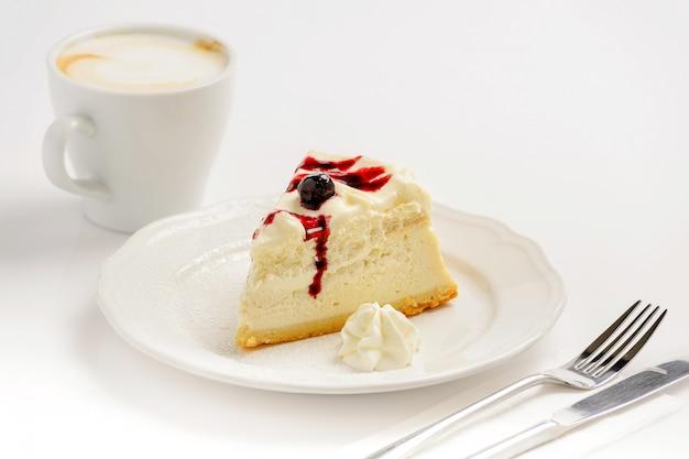 Deliciosa tarta de queso con mermelada y una taza de capuchino