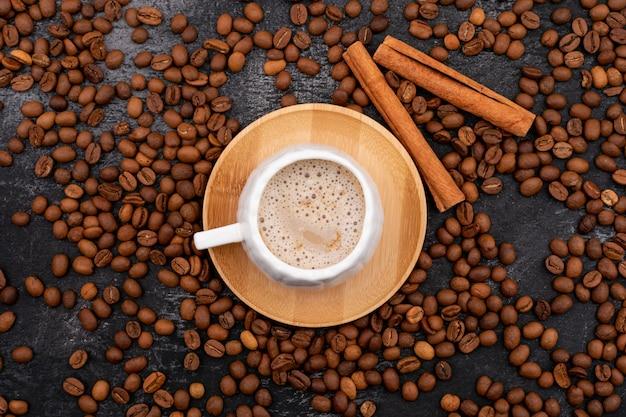 Deliciosa taza de café capuchino rodeado de granos de café tostados en piedra negra