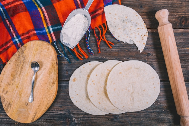 Deliciosa tortilla mexicana de trigo; rodillo de madera; cuchara; paño; harina y tabla de cortar en mesa de madera.