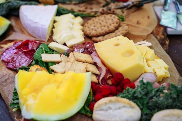 Deliciosa variedad de aperitivos, queso, jamón, fruta fresca y bayas.
