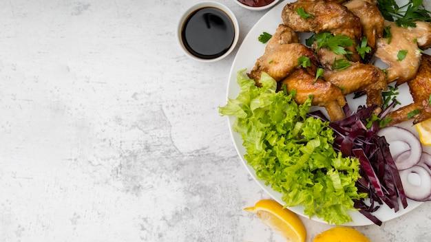 Deliciosas alitas de pollo con ensalada y espacio de copia