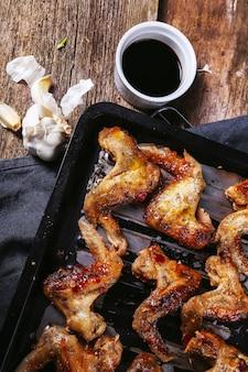 Deliciosas alitas de pollo en la mesa de madera