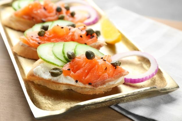 Deliciosas bruschettas de salmón en bandeja de metal, primer plano