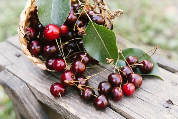 Deliciosas cerezas en banco de madera